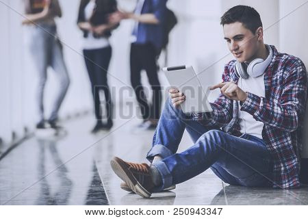 Young Student Is Studying In Hall With Tablet. Studying Young Man. Education And Career Concept. Stu