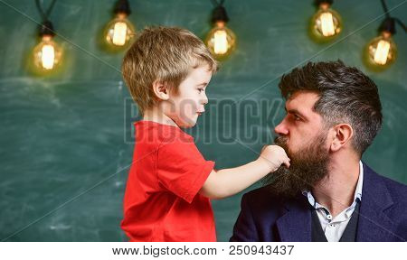 Teacher with beard, father and little son having fun in classroom, chalkboard on background. Dad with beard spend time with son. Child cheerful play with beard of teacher. Fatherhood concept. poster