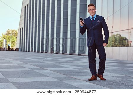 Full Body Portrait Of A Confident Businessman Dressed In Elegant Suit Holds A Phone While Standing A