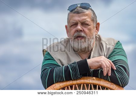 Outdoor Portrait Of Senior Man In Black Sunglasses Leant On A Wicker Chair Against Cloudy Sky