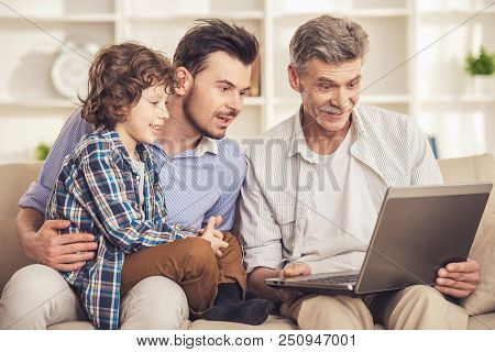Generation Men look in Laptop. Surprized Grandfather. Grandfather Father and Grandson. People on Sofa. Professional Family Portrait. Happy Femily. Tolking Men. Smiling Child with Parents. poster