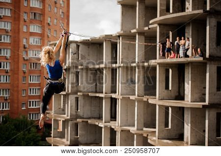 Rear view blondie woman bangling on the slackline rope on the background of house and unfinished building poster
