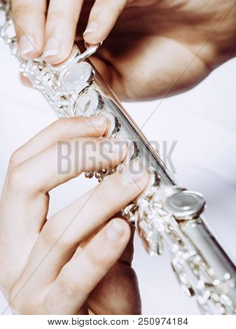 Hands Of Young Man Playing The Flute. Male Flutist Musician Performer Holding Instrument, Close Up