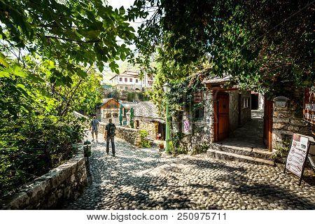 Mostar, Bosnia And Herzegovina - October 1 2017: Tourists Walk A Cobblestone Path Over A Bridge In T