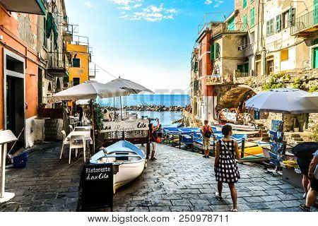 Riomaggiore, Italy - September 18 2017: Tourists Enjoy A Sunny Day On The Ligurian Coast With The Se