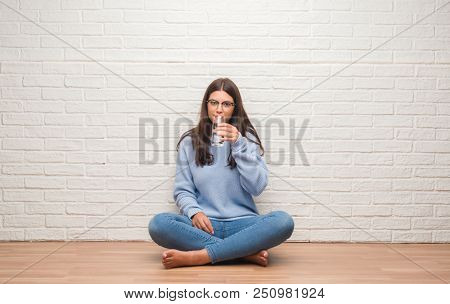 Young brunette woman sitting on the floor drinking glass of water with a confident expression on smart face thinking serious