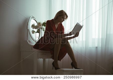 Studying Poetry. Sexy Woman Studying Poetry Sitting In Bedroom. Studying Poetry At Home. Girl In Red