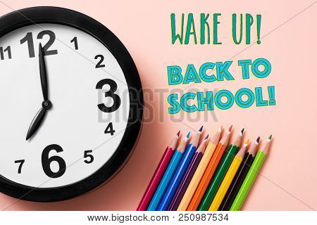 closeup of a clock, some pencil crayon of different colors and the text wake up back to school on a pink background