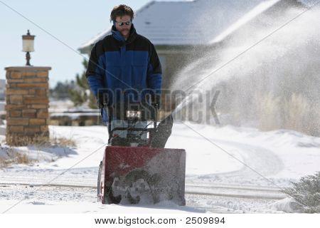 Man Snowblowing In Wintertime