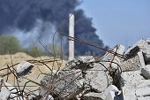 A pile of concrete rubble with protruding rebar on the background of thick black smoke in the blue sky. Background. The concept of the consequences of human activities. poster