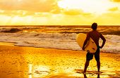 Saturated and stylised rear view of young man male surfer with white surfboard looking at surf on a beach at sunset or sunrise poster
