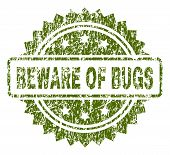 BEWARE OF BUGS stamp seal watermark with rubber print style. Green vector rubber print of BEWARE OF BUGS text with dust texture. poster