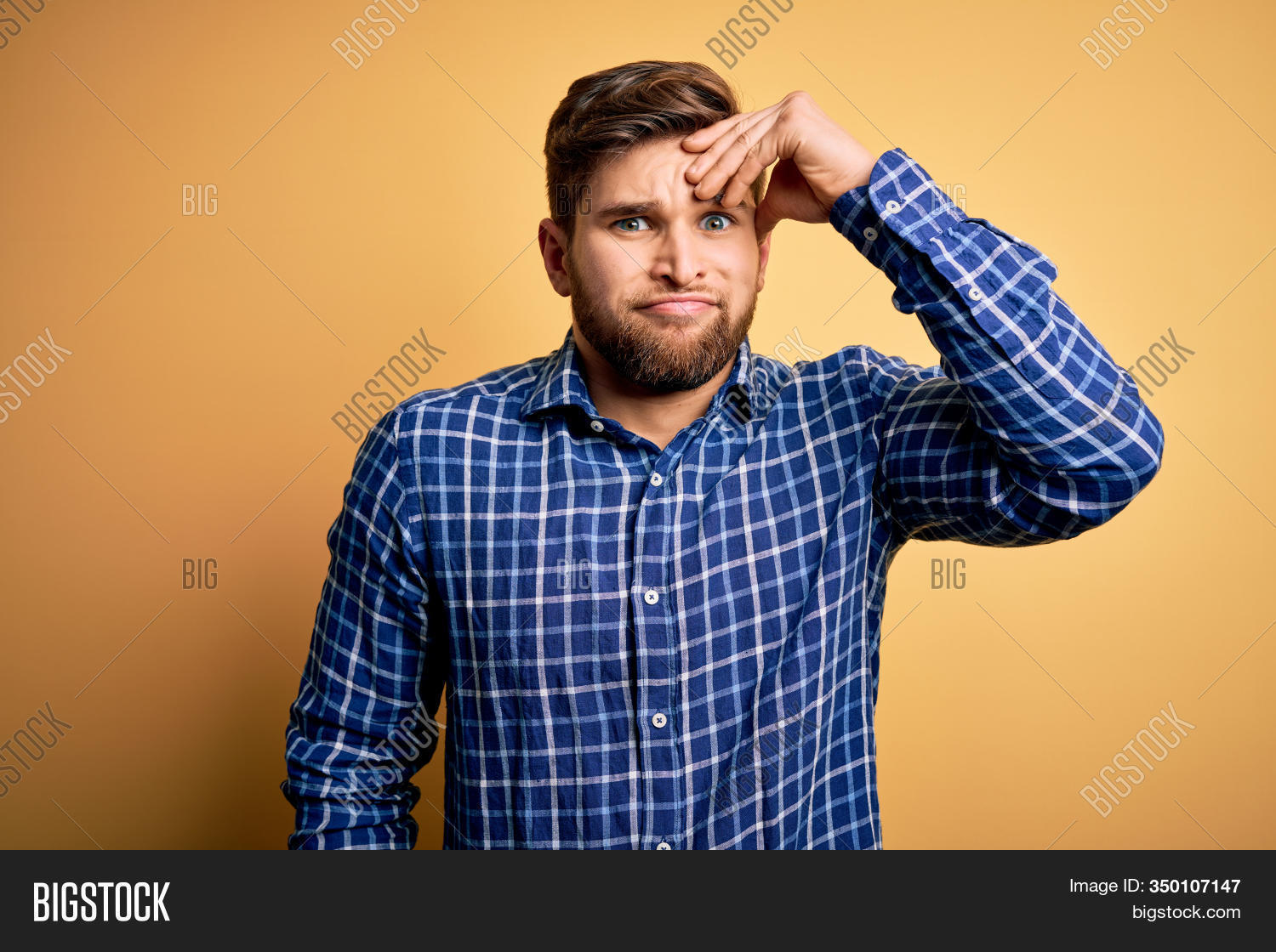 Young blond businessman with beard and blue eyes wearing shirt over yellow background worried and stressed about a problem with hand on forehead, nervous and anxious for crisis