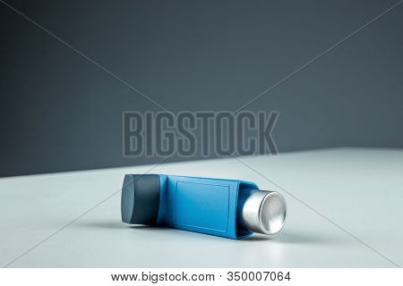 An Asthma Inhaler Lies On A White Table Against A Gray Background, An Asthmatic Attack. The Concept