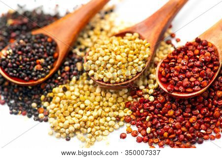 Black, red and white quinoa grains in a wooden spoon isolated on white background. Gluten free Healthy food. Seeds of white, red and black quinoa - Chenopodium quinoa closeup