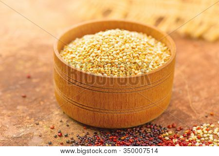 Quinoa White grains in a wooden bowl. Gluten free Healthy food. Diet, dieting concept. Seeds of white, red and black quinoa - Chenopodium quinoa. Vegan food