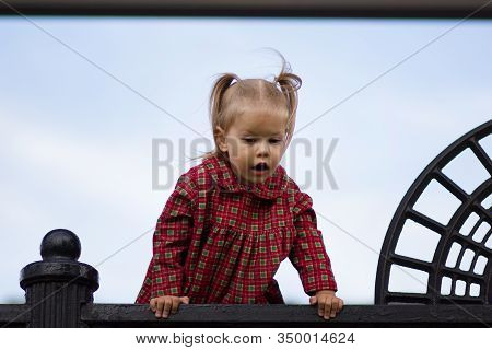Portrait Of Curiosity Caucasian Child Of Two Years Old Looking Down From High Point On The Blue Sky