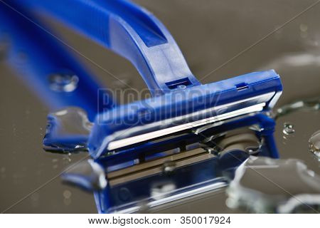 Macro view of safety razor blade on water drops background.  Shave blade razor close up  on gray mirror wet surface