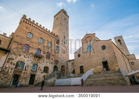 San Gimignano, Italy - February 8, 2020: View At The Cathedral Of Santa Maria Assunta With Town Hall