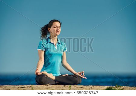 Relaxed Young Woman Meditating While Sitting On Sandy Shore In Lotus Pose