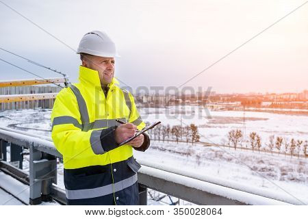 A Smiling Caucasian Builder In A White Hard Hat And Yellow Fluorescent Jacket Holds Clipboard, Stand