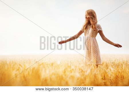 Girl With Blond Wavy Hair In White Lace Dress, Posing On Wheat Field And Looking Away. Blurred Backg