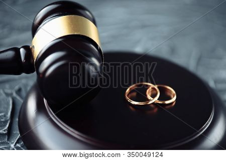 Two Broken Golden Wedding Rings Divorce Decree Document. Divorce And Separation Concept