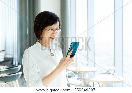 asian female using smart phone in office beside window
