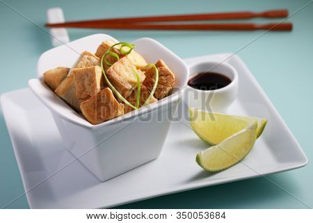 Fried tofu served with soy sauce, slices of lime, and green onion on a porcelain styled like take away box