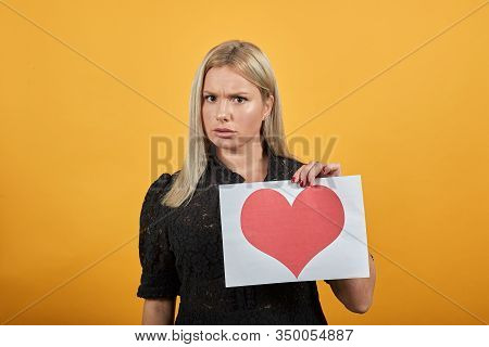 Beautiful Blonde Girl In Black Dress On Yellow Background Upset Woman Dissatisfied Holding Piece Of