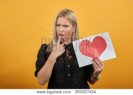 Beautiful Blonde Girl In Black Dress On Yellow Background Holds A Piece Of Paper With Red Heart And