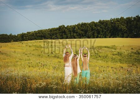 Three Girls With Wreaths Of Mehendi Flowers On Their Hands In The Style Of Boho In The Field On A Su