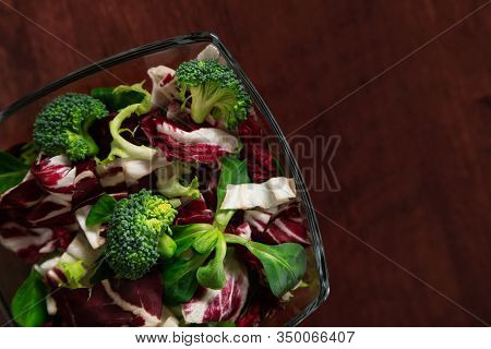 Shredded Ingredients For Organic Salad Of Frisse, Broccoli, Radicchio, Onion, Olive Oil In Glass Bow