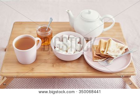 Breakfast In Bed In Hotel Room. Accommodation. Breakfast In Bed With Tea Cup With Pancakes On Tray O