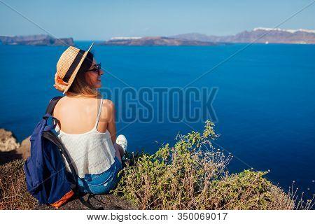 Woman Traveler Sitting On Edge Of Rock Looking At Caldera, Aegean Sea From Akrotiri, Santorini Islan