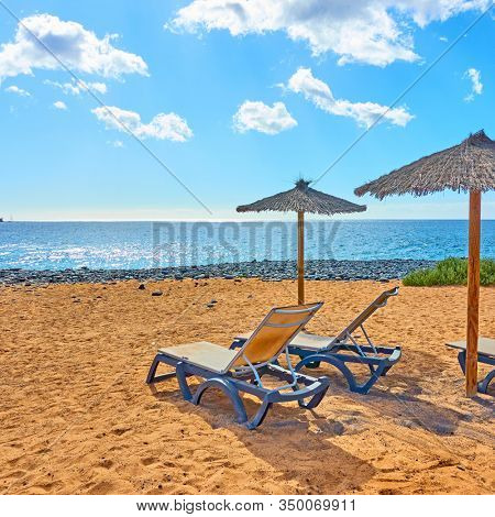 Sandy beach with parasol and chaise longues by the sea