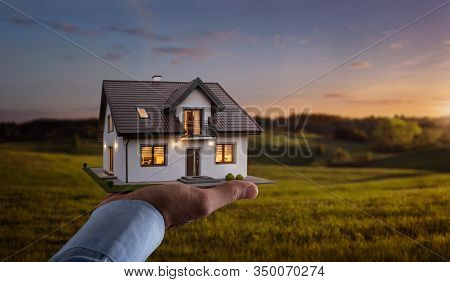 Concept Of Buying Or Building New Home. Male Hand Showing, Offering A New Dream House At The Empty F