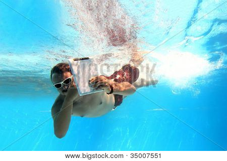 Man underwater holding a tablet PC