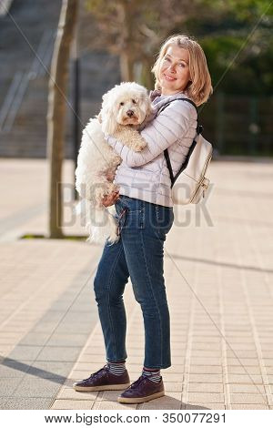 Mature Woman Walking With Fluffy White Dog In Summer City