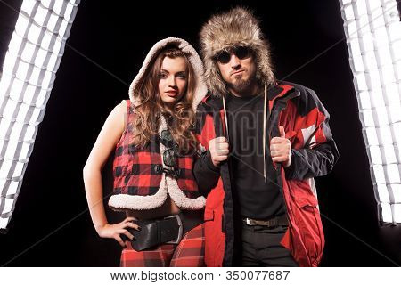 Front View Of Pretty Lady Standing Beside Man In Sunglasses. Charming Girl In Hooded Vest Posing Wit