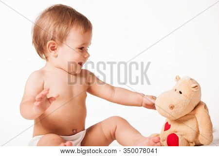 Front View Of Adorable Kid Playing With Bear Toy. Isolated On White Studio Background. Concept Of Ed