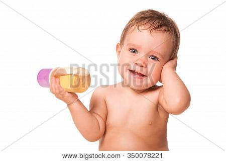 Front View Of Adorable Little Boy Holding Bottle Of Baby Food. Cheerful Kid Covering Ear With Hand A