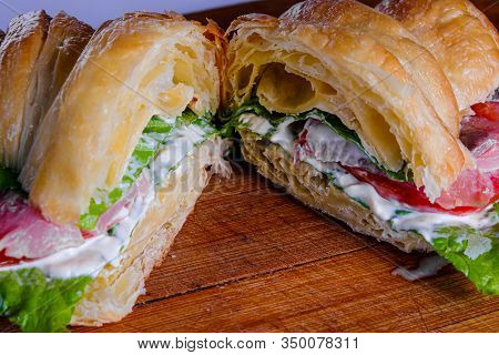 Croissant Sandwiche With Salmon Red Fish On A Wooden Background