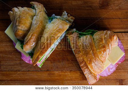 Croissant With Ham And Cheese Isolated On A Wooden Background