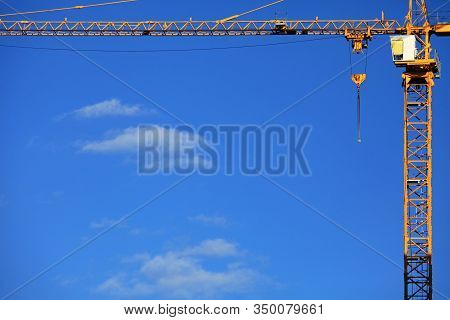 Single High-rise Construction Crane On The Blue Sky Background. Building Construction Site With Cran