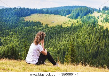 Girl Sitting On Top Of A Mountain And Admiring The Beauty Of Nature