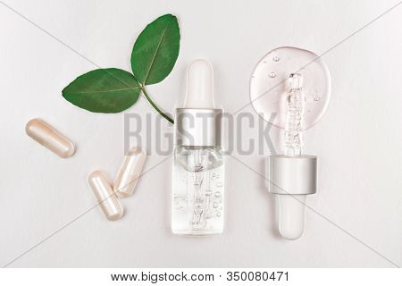 Bottle With Hyaluronic Acid On Silver Background. Concept Of Modern Beauty. Flat Lay Style.