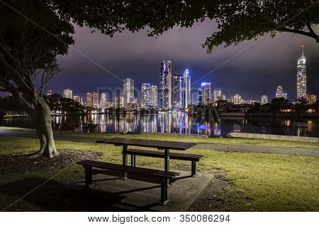 Surfers Paradise City Skyline On Dusk Framed By Trees With A Park Bench In The Foreground, Gold Coas