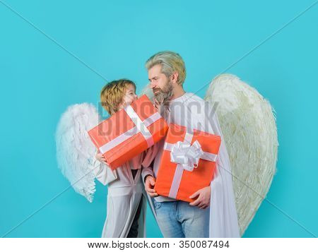 Happy Father In Angel Costume With Little Son Angel Holds Present. Valentines Angels With Gift Box.