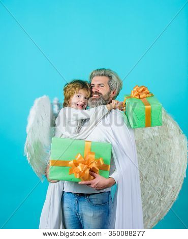 Little Angel Boy Gives Father Gift. Happy Father In Angel Costume With Little Son Angel Holds Presen